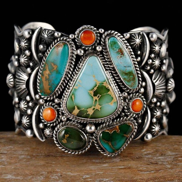 Beautiful Navajo cuff with detail silver work and turquoise and coral - Cuff, Daryl Bacenti. For this bracelet, Darryl has made his own stamps and dyes, and heavily employed magnificent stars, fans, scallops, shells, and elaborate appliques onto the surface of the bracelet cuff. This cuff features a stunning cluster of natural Royston turquoise cabochons. This Cuff is SIGNED by Darryl Becenti and Weighs in at a HEFTY 138 Grams