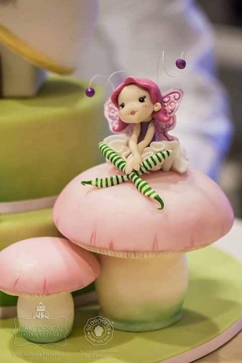 This fairy is part of a wonderful fairy house cake by Lalla's Cake - di Manuela Blasi. See the complete cake on  https://www.facebook.com/pages/Silovoglio/ (it's photo 102 in the Cake Design Italian Festival 3rd edition album of 145 photos).