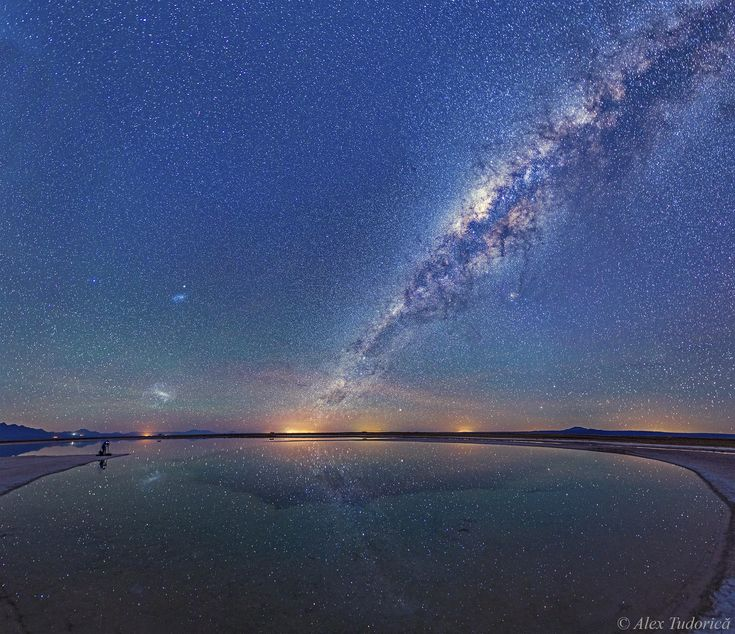 Milky Way above Atacama Salt Lagoon-Chile Image Credit & Copyright: Alex Tudorica (AIfA, U. Bonn) The featured panorama is a 12-image mosaic taken last month from the Salar de Atacama salt flat in northern Chile. The calm water is Laguna Cejar, a salty lagoon featuring a large central sinkhole.  The night sky is lit up with countless stars, the Large and Small Magellanic Cloud galaxies on the left, and the band of our Milky Way galaxy running diagonally up the right.