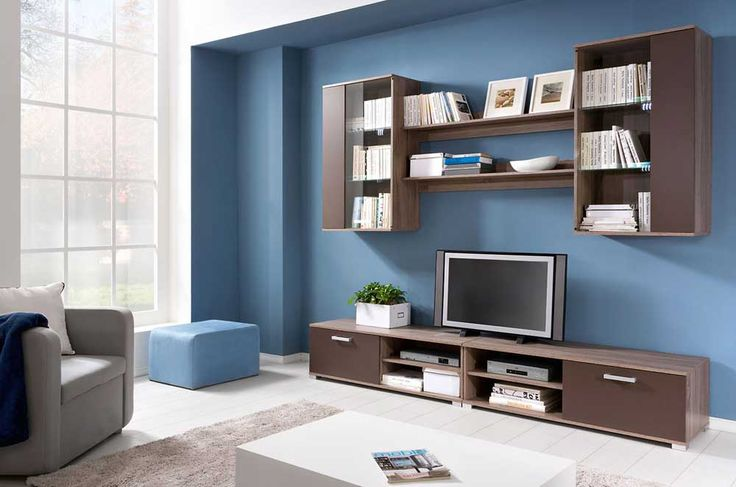 Cupboard Wall Pic with storage book attached to the blue wall and brown wooden rectangle tv table above white tile floor