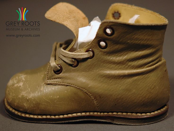 A pair of toddler-sized boots. They are from the 20th-century, likely from before the 1960s. The underside of the sole has a suede leather. Grey Roots Museum & Archives Collection.