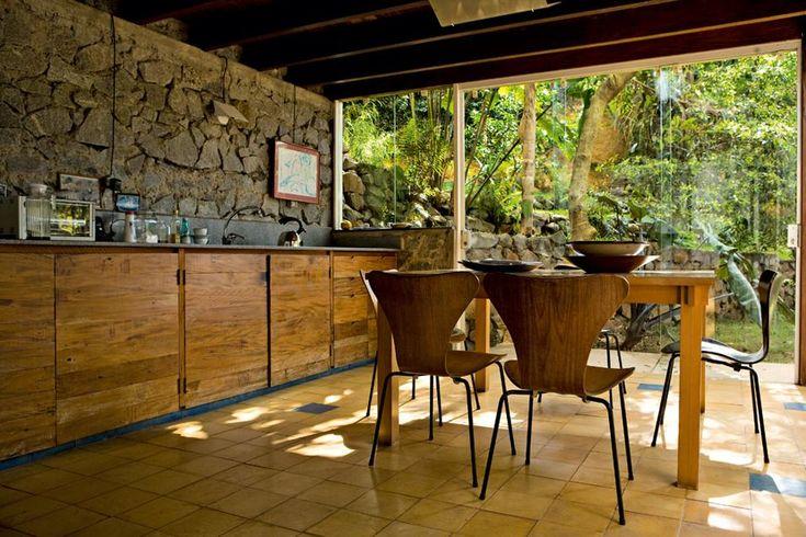 SAN PAOLO | In cucina una parete di pietra a vista, travi di legno e le immancabili vetrate che si aprono sul giardino. Tavolo e bancone li ha progettati Rafic Farah, le sedie sono le N.7 di Arne Jacobsen, 1955, per Fritz Hansen