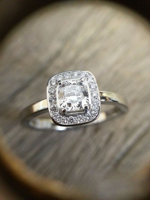 Cushion cut diamond halo platinum engagement ring.