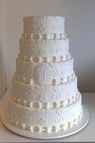 Bolo redondo de cinco andares branco coberto de pasta americana e decorado com trabalho imitando renda em glacê, Wayne Ferreira.Preço:R$ 130 o quilo Foto: Divulgação
