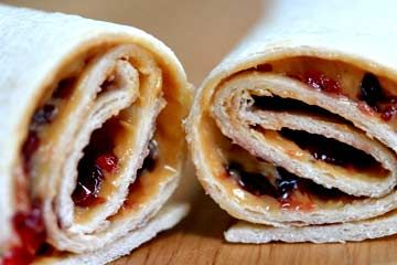 Kid friendly wraps recipes including peanut butter and jelly wraps and cream cheese, sliced ham, and shredded carrots wraps.  Roll-ups made with flour tortillas and various fillings.
