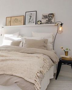 Simple white bedroom, soft lighting and personalised art along the shelving.