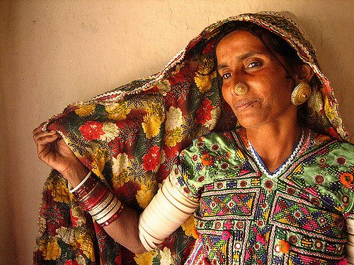 """A Meghwal tribal from the northern Kutch village of Ludiya. As with most of the tribal villages throughout the Kutch region, they have a distinct style of textile work that they wear.  I had also photographed her last year. She is 50 years old and has 9 children. Her husband adds """"enough for a cricket team""""(including themselves or their 2 grand-children)"""