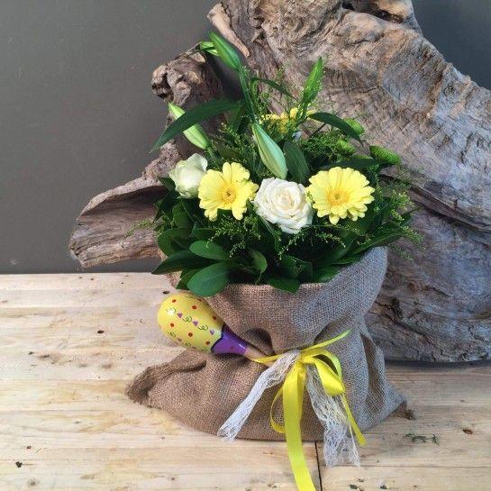 Πουγκί από τσουβάλι με κίτρινα ζερμπερίνια, λευκό λίλιουμ, τριαντάφυλλα, λαχανί χρυσάνθεμα και σολιντάγκο.Το δέσιμο είναι από κίτρινη σατέν κορδέλα και ιβουάρ δαντέλα.Στο δέσιμο υπάρχει παιδική κουδουνίστρα. http://nedashop.gr/anthopoleio/gennisi?product_id=431