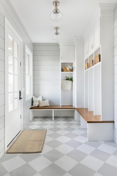 Charming gray and white mudroom features white and gray harlequin floor tiles accenting light gray shiplap walls lit by two glass schoolhouse flush mount lights.