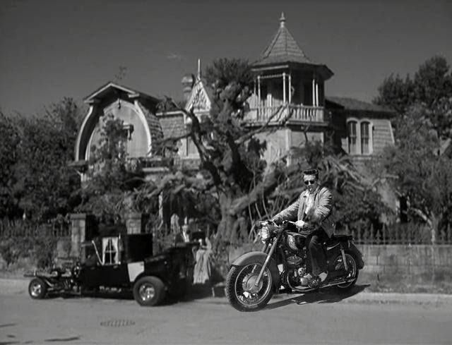 James Dean the Giant riding on his 1955 Triumph Trophy parked in front of 1313 Mockingbird Lane