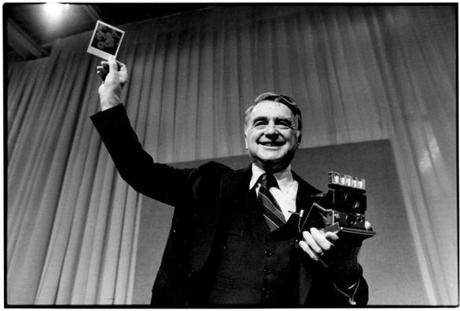 Dr. Edwin H. Land, Chairman of the Board and Director of Research of Polaroid Corporation, holds up a color photograph he took moments earlier with the new Polaroid SX-70 film that produces a fully developed print in about one minute. Dr. Land demonstrated the super fast SX-70 film at Polaroid's annual shareholders' meeting. This is one of the most important new developments we have ever made, and we'r working
