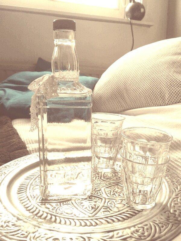Jack Daniels fles, etiketten eraf gehaald en lintje om de hals geknoopt. Met dienblad en kleine glaasjes heb je zo iets leuks voor op tafel!  :)
