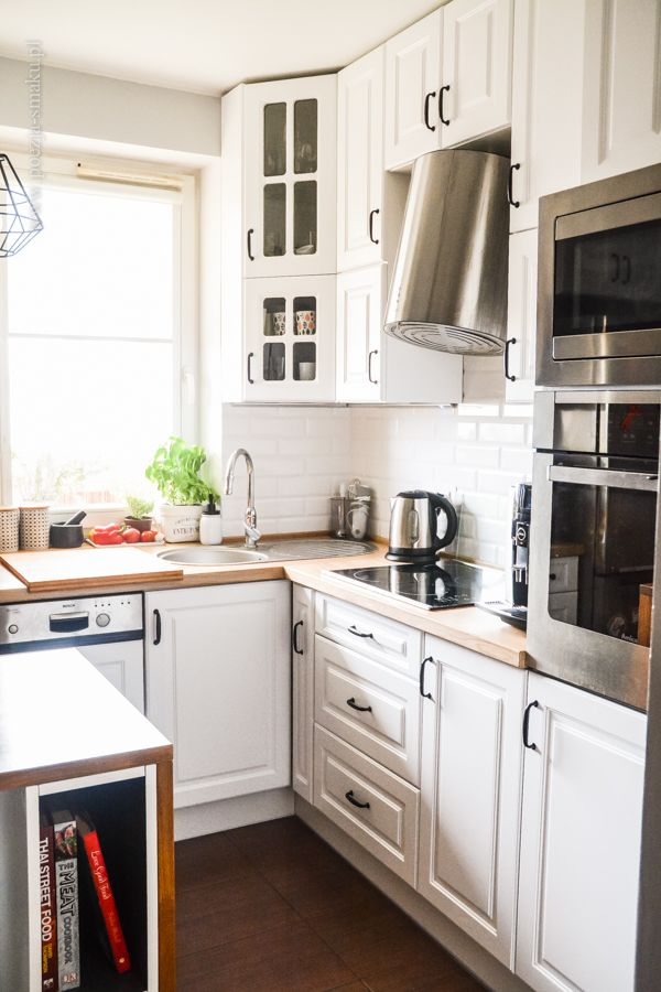 Mała kuchnia w bloku: białe fronty, drewniany blat, kafelki metro / Small kitchen: wooden working table, white cabinets and white tiles