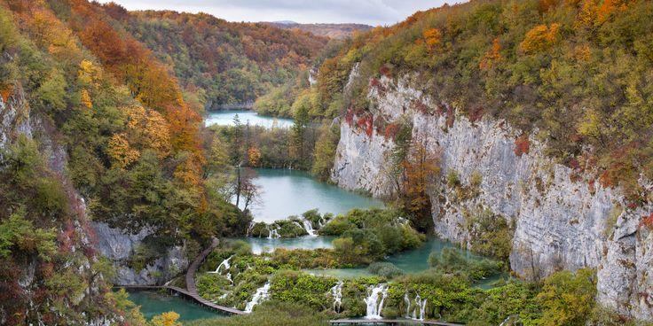 The bright blue waterfalls of Croatia's Plitvice Lakes National Park pop against the fall foliage