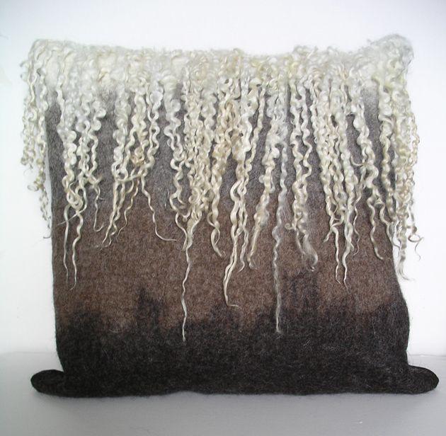 Shetland cushion shaded from natural white through grey, moorit and black. Natural Teeswater locks felted along top edge.