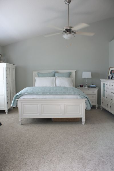 Blue-grey bedroom with white painted furniture.
