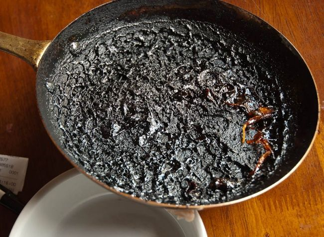 Aangebrande pan schoonmaken:              Fill the frying pan with a little water — only enough to cover the surface area. Then pour in a glass of vinegar. Boil thoroughly on a medium heat, then remove from the stove and add two tablespoons of baking soda. The burnt bits of food will come off with no trouble at all.