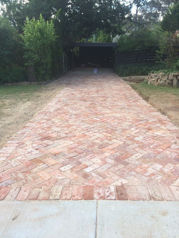 The future redbrick driveway giving character and a rustic edge to the white hampton facade