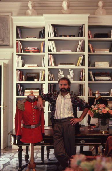 Fashion designer Gianni Versace (1946 - 1997) with a dressmaker's dummy in military uniform at his home on Lake Como, June 1983.