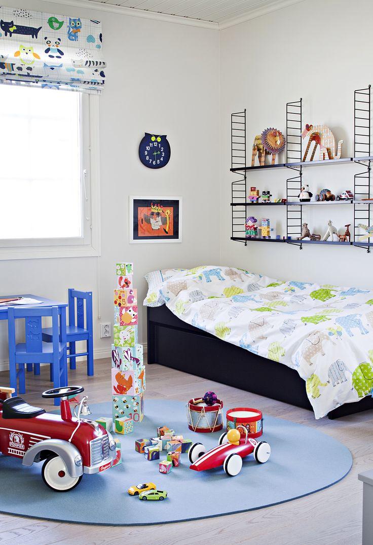 Huoneen kantavat värit ovat valkoinen, musta ja vaaleansininen. Muut värit elävöittävät kokonaisuutta. Pyöreä matto on hyvä alusta monelle leikille.