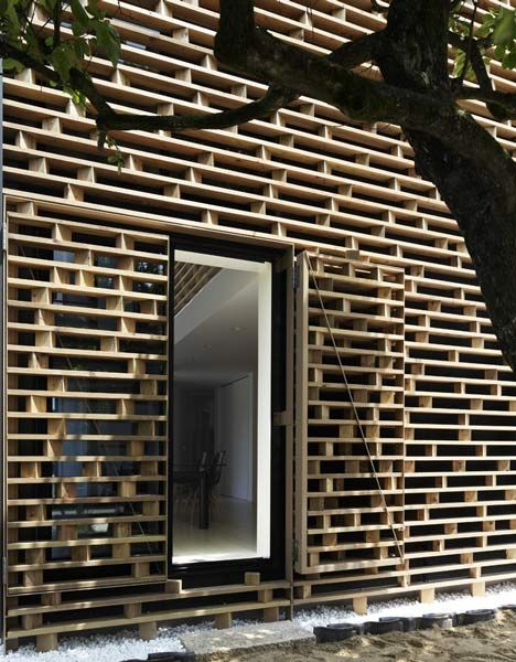 A grid of timber louvres screens the end facades of this Japanese house by architects AE5 Partners.