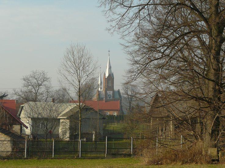 Kościół parafialny skryty za budynkiem plebanii
