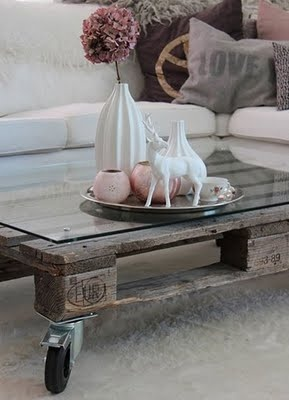 distressed shipping pallet put on casters and used as a coffee table