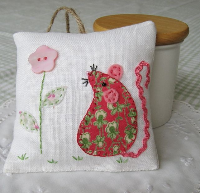 A sweet little lavender bag to scent your room, drawers or wardrobe with fresh, summery fragrance. It is carefully handsewn and embroidered with a cheeky little floral mouse with a wiggly ribbon tail, a beady eye and whiskers.