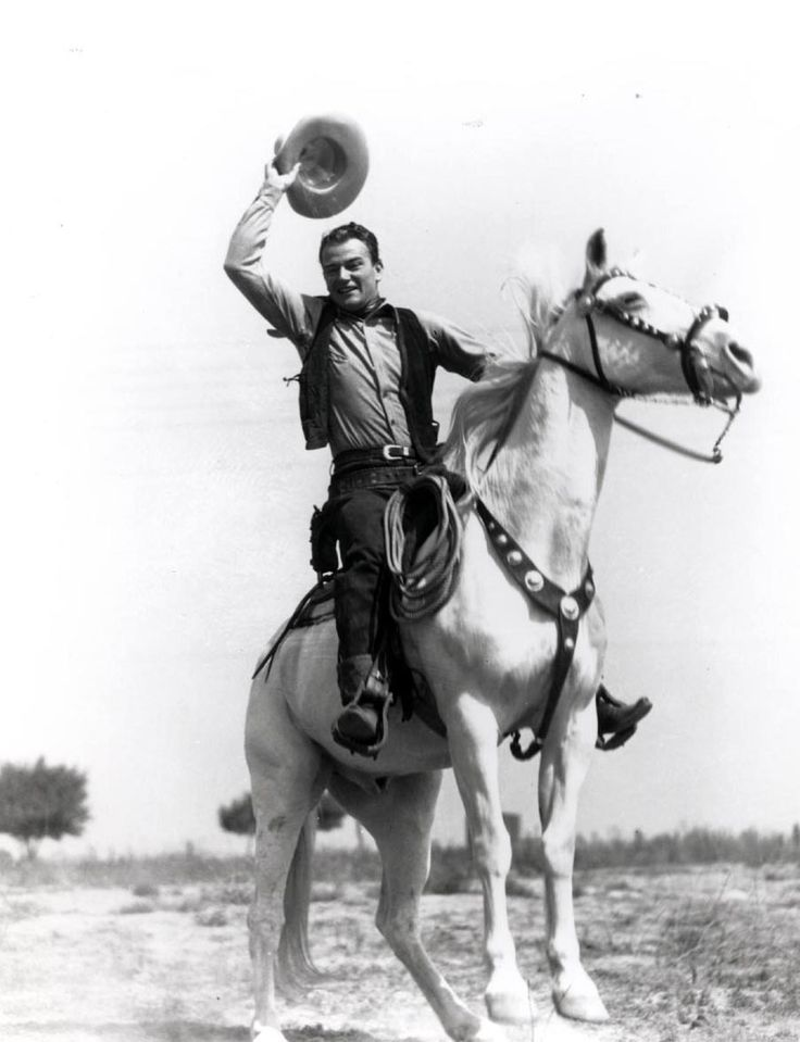 """John Wayne, Nicknamed: """"The Duke"""". Always used his very own horse named, """"Dollar"""" in all movie's were he rode a horse. (Dollar is featured in this photo being ridden by John)."""