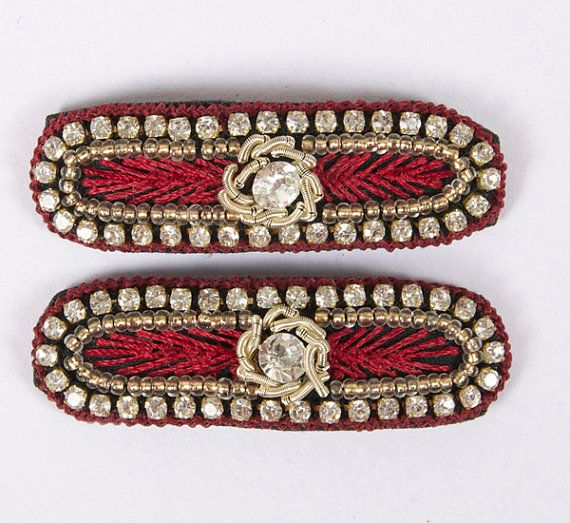 """A beautiful pair of hand embroidered elongated oval shape snap clips-""""tick tock clips"""". Maroon thread edging with diamonds and gold beading embroidery with one big diamante in the center. Snap clip, diamantes, hand embroidered. Maroon, Gold, Beading, Diamante, Round Crystal. Rectangle with rounded edges; Approx. 1 1/2 inches length by 1/2 inch width Unique and beautiful on young girls and adults. £8.00 on Etsy... Please click on the Etsy link to purchase."""