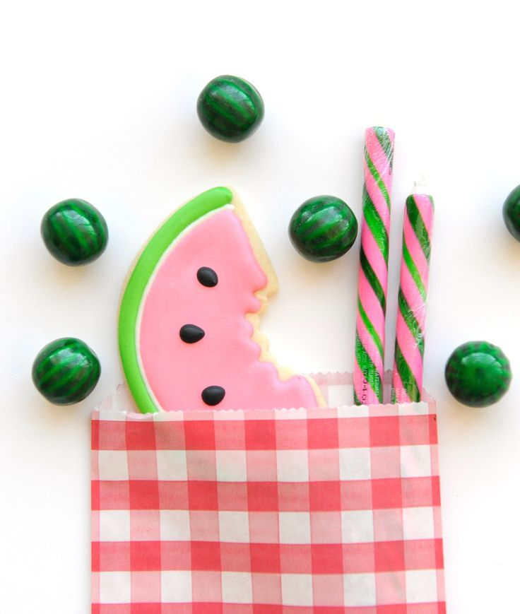 Cookie and candy watermelon themed birthday party goodie bags. Red and white gingham paper gift bag. Pink and green watermelon sweet candies. Summer Watermelon Party styling by Happy Wish Company. Photography by Tammy Hughes Photography. Stationery by Minted artist, Oma N. Ramkhelawan.
