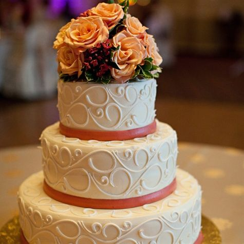 Round 3 Tier Cake with decorative scrolls, coral ribbons and around each tier and peach roses as the topper.