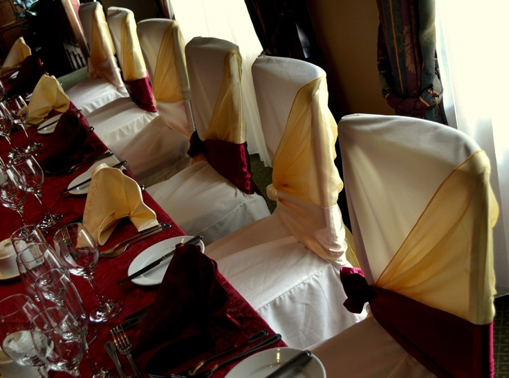Gold Organza Shawls with alternating Ivory Satin and Burgundy Satin Bows on Ivory Chair Covers