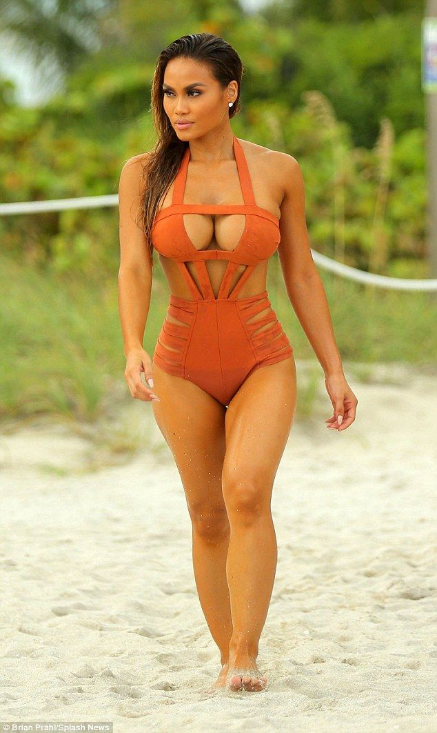 Hot in orange:The 5ft6in beauty was lounging on the beach in an orange cut-out suit...