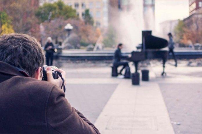 Fotografo tomando un foto a un pianista en la calle.