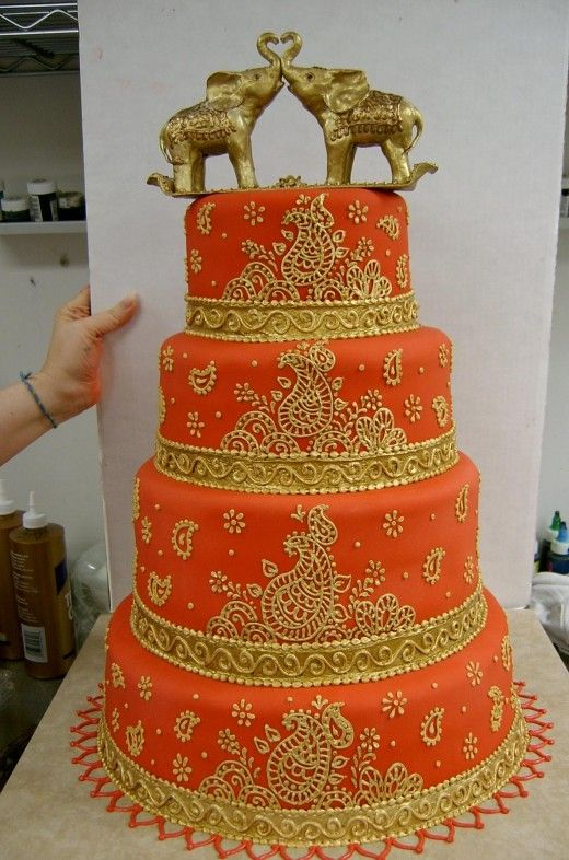 Orange and Gold Indian Wedding Cake  Indian Cake  Source: Deviantart - Evil Plankton  About This Wedding Cake    This gorgeous looking wedding cake is decorated with floral designs (more like a Henna tattoo design). Can you believe that the elephants at the top are made out of gum paste? They are then coated with an edible pearl powder