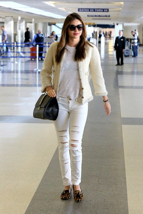 Miranda Kerr wears a white t-shirt, distressed white skinny jeans, a black Valentino bag, Chanel tweed jacket, and leopard print loafers