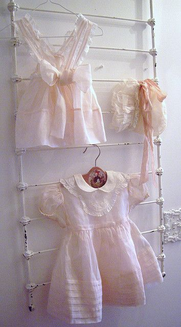 Vintage baby clothes are my favorite. I like the rail used to hang the garment.  vintage baby dresses and bonnet by skblanks, via Flickr