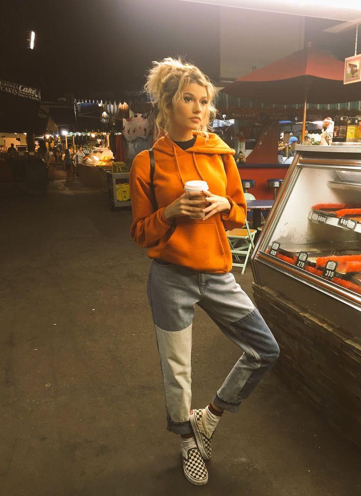 Orangefarbener Hoodie und karierte Sneakers mit fleckigen Jeans