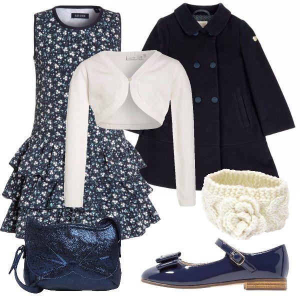 Un outfit elegante, per una domenica in famiglia o una cerimonia per cui le nostre piccole principesse non rinunciano a fare bella figura. Un abito smanicato blu, con fiorellini chiari bianchi e azzurri, con scaldacuore bianco. Ai piedi una ballerina con cinturino, di vernice blu. Per uscire, un cappotto a campana blu, con colletto e bottoni tono su tono, in testa una fascia in lana chiara e una borsetta blu, a forma di gatto.