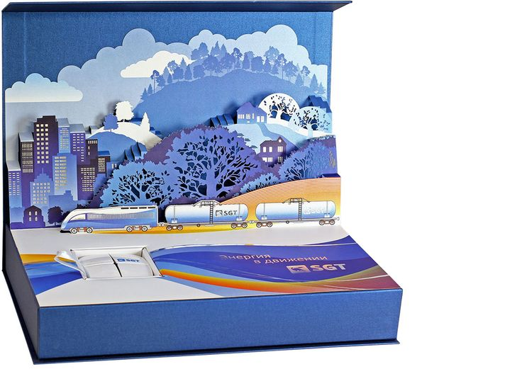 Подарочная коробка Энергия в движении. В простой на вид коробке притаился вау-эффект: из-под плоской крышки вырастает объемный город. Как в детских чудо-книжках. Пейзаж с вагончиками, везущими энергию тепла и уюта в деревушки и мегаполисы, выполнено в технике киригами.