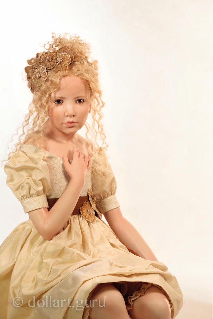 Кукла выполнена из высококачественного фарфора, покрытого воском. Парик из светлых вьющихся натуральных волос. Прическа украшена цветами из бархата на шелковой ленте. Ручной работы карие глаза из стекла.  На кукле нарядное светло-бежевое шелковое платье с декоративными бархатными цветами на поясе.  У девочки в руках игрушка — антикварная кукла Bru с музыкальной шкатулкой «Ute Mareczek».