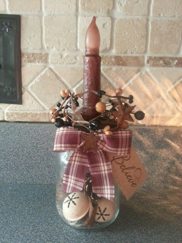 Mason jar filled with jingle bells, cinnamon stix, pine cones. With berry ring and battery operated grunged candle.