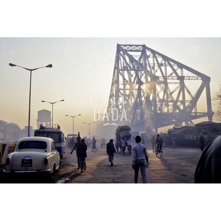 """Situato nel distretto di Howrah, nella città indiana di Kolkata, Howrah Bridge è stato per molti anni l'unico accesso a Calcutta. Nencini testimonia con """"Howrah Bridge"""" l'avanzata del moderno. La rete in acciaio, che s'innalza verso il cielo, è la protagonista indiscussa. Nascondendo il sole, permette all'artista di realizzare un'opera dalle sfumature grigie e aranciate senza precedenti.   Calcutta, 1994"""