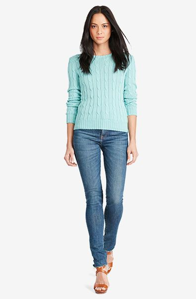 Woman wears sea foam green cable-knit crewneck sweater and jeans.