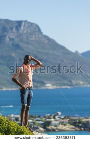 http://www.shutterstock.com/pic-226382371/stock-photo-african-black-man-standing-on-a-high-rock-overlooking-cape-town-as-he-points-and-scouts-the-blue.html?src=WuffEuvvGWj02MQSGcnIHQ-1-20 African Black Man, Standing On A High Rock Overlooking Cape Town As He Points And Scouts The Blue Sky, Ocean And Mountains On A Sunny Summers Day Stock Photo 226382371 : Shutterstock