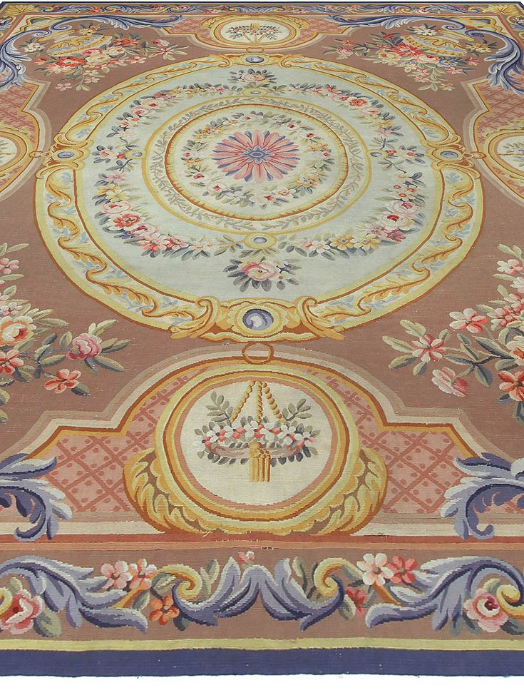 This antique French Aubusson rug features a large oval medallion against a brown field and ornate floral designs borrowed from a style steeped in a long carpet and tapestry-weaving tradition. The Aubusson, Creuse commune of France is renowned for tapestry manufacture. Typically, Aubusson carpets depended on engravings as a design source or the full-scale cartoons from which the low-warp tapestry-weavers worked. Figures were set against a conventional background of verdure, stylized foliage…
