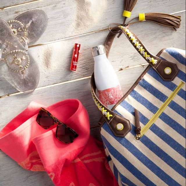 Get beach ready: A stripe beach tote, bright coral towel, tortoise shell sunglasses for style, a crown & ivy water bottle to stay hydrated, silver Jack Roger jellies, and benebalm for your lips.
