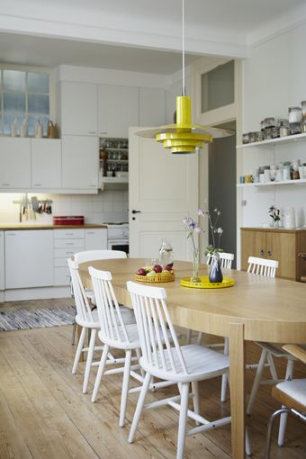 white and light wood kitchen and dining table with neon yellow accents