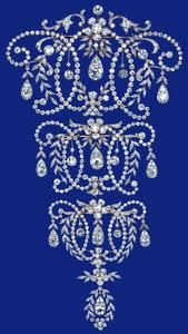 QUEEN MARY'S STOMACHER The stomacher, made at London jeweler Garrards,  is formed as three linked brooches which can be worn separately. Made for Queen Mary in 1920 with diamonds from two of her wedding presents: the 'Kapurthala' stomacher and the 'Town of Swansea' crescent, both given in 1893. Given by Queen Mary to Princess Elizabeth for her wedding in 1947.